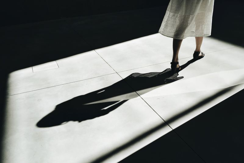 A woman wearing a white dress is in the process of leaving, showing her shadow following behind her.