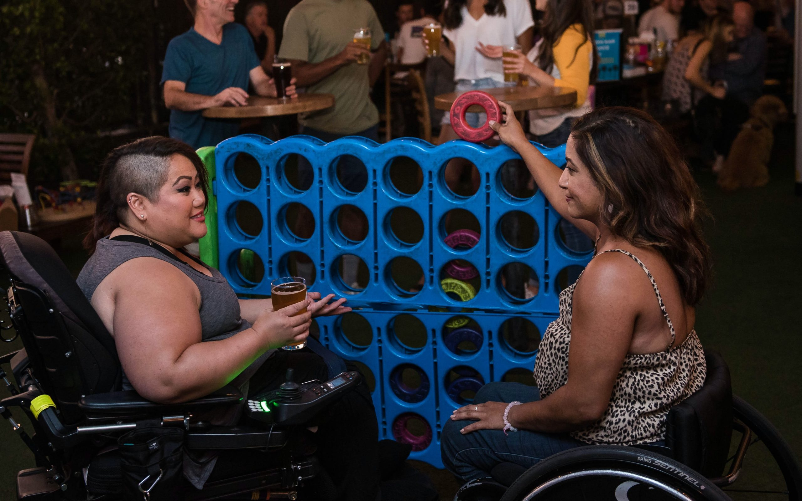 Two people with tan skin each sit in their wheelchairs, talking casually. One holds a glass of beer and the other holds a ring over the large-sized game of connect four that