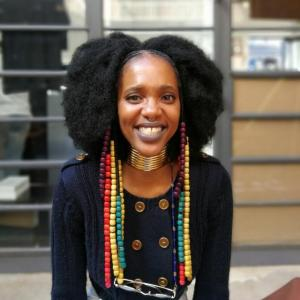 A dark-skinned woman with black natural hair parted down the middle smiles widely at the camera. She wears a black longsleeve shirt with gold buttons, gold hoops around her neck, and long strings of brightly colored beads attached to her earrings.