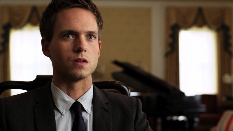 Character Mike Ross: A young white man with cropped brown hair, wearing a grey business suit and tie, a grand piano out of focus behind him. He is looking intently at something off camera and his expression is one of disbelief or shock.