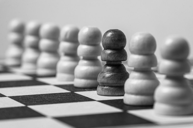 Black and white photo of a straight line of wooden chess pawns on a chess board. All but one are white, and only the black one is fully in focus.