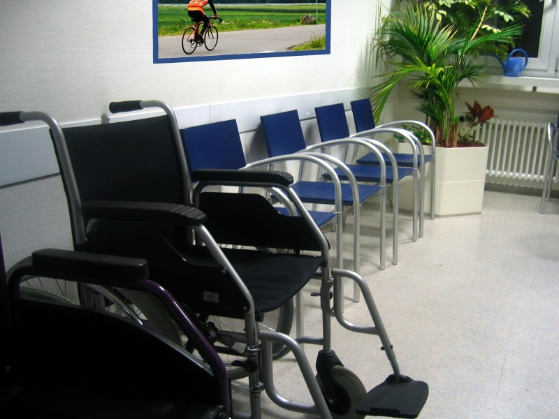 A doctor's waiting room filled with empty blue chairs that all look the same except for one larger black wheelchair at the front of the row.