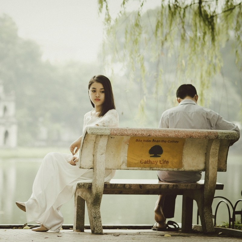 A young couple wearing white sit on opposite sides of a bench, facing away from each other, next to a mossy body of water.