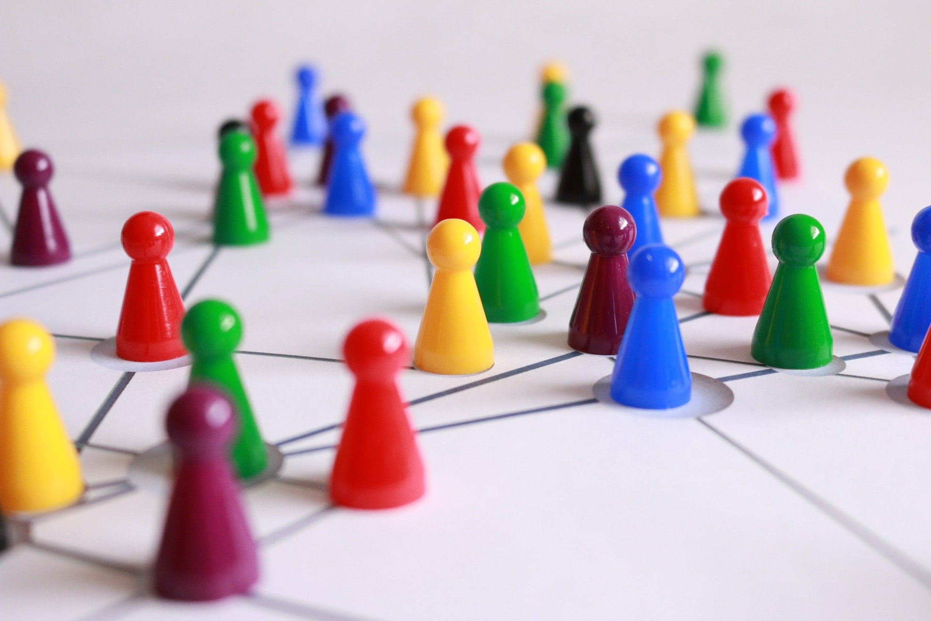 More than twenty plastic game pieces in many different colors are arranged on a board, with lines drawn between them to mark the complex network that ties them together.
