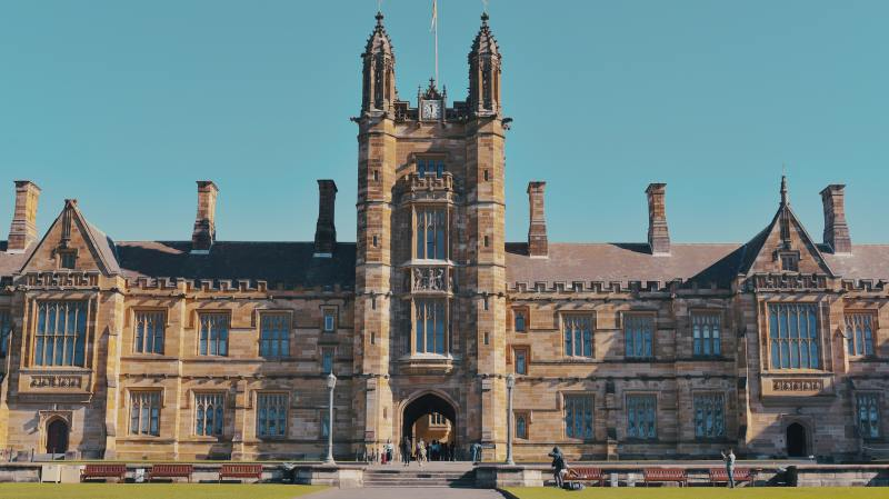 A wide shot of the University of Sidney: a long stone building that's varying shades of tan with two stories and a slanted roof except for the double columned tower in the center, which has a large archway at ground level.