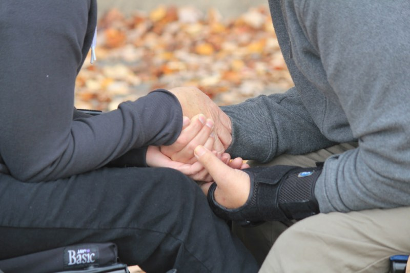 A romantic couple each sits in their respective wheelchairs, grasping hands over their kneeds in the center. They are both wearing grey casual clothing, and one of them has a black wrist brace on.