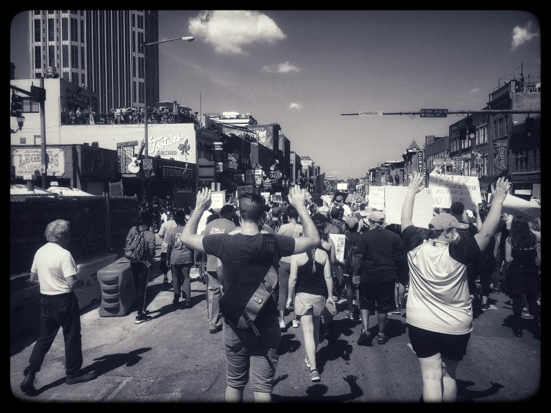 Black and white photo from Nashville, TN BLM protests. Looking at the backs of a large crowd of people walking in the middle of the street many with their hands raised in the air as if in surrender, or holding signs.