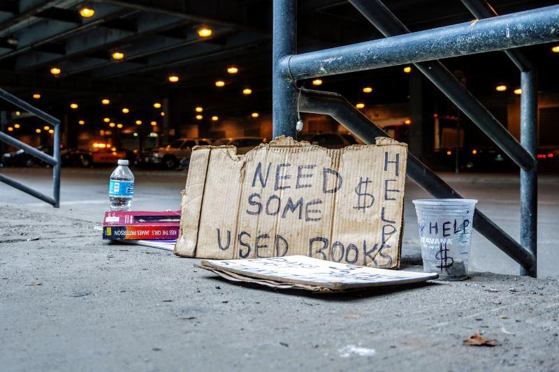 """A cardboard sign rests on the ground next to a pole. In sharpie, it says """"Need some used books. Help."""" There is a plastic cup for collecting money next to it."""