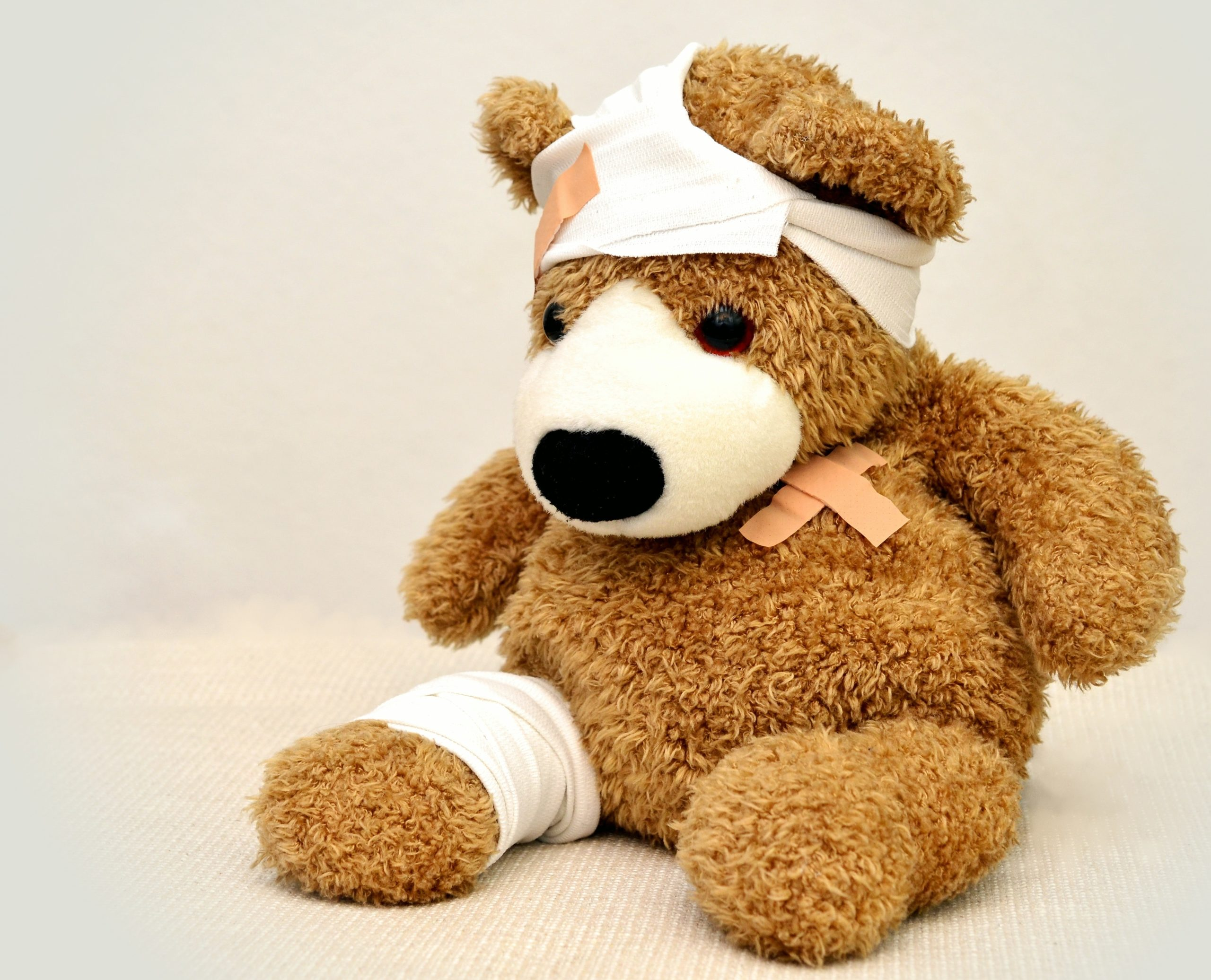 A light brown fuzzy teddy bear has wrappings and bandages on his left, over his heart, and around his head, as if he