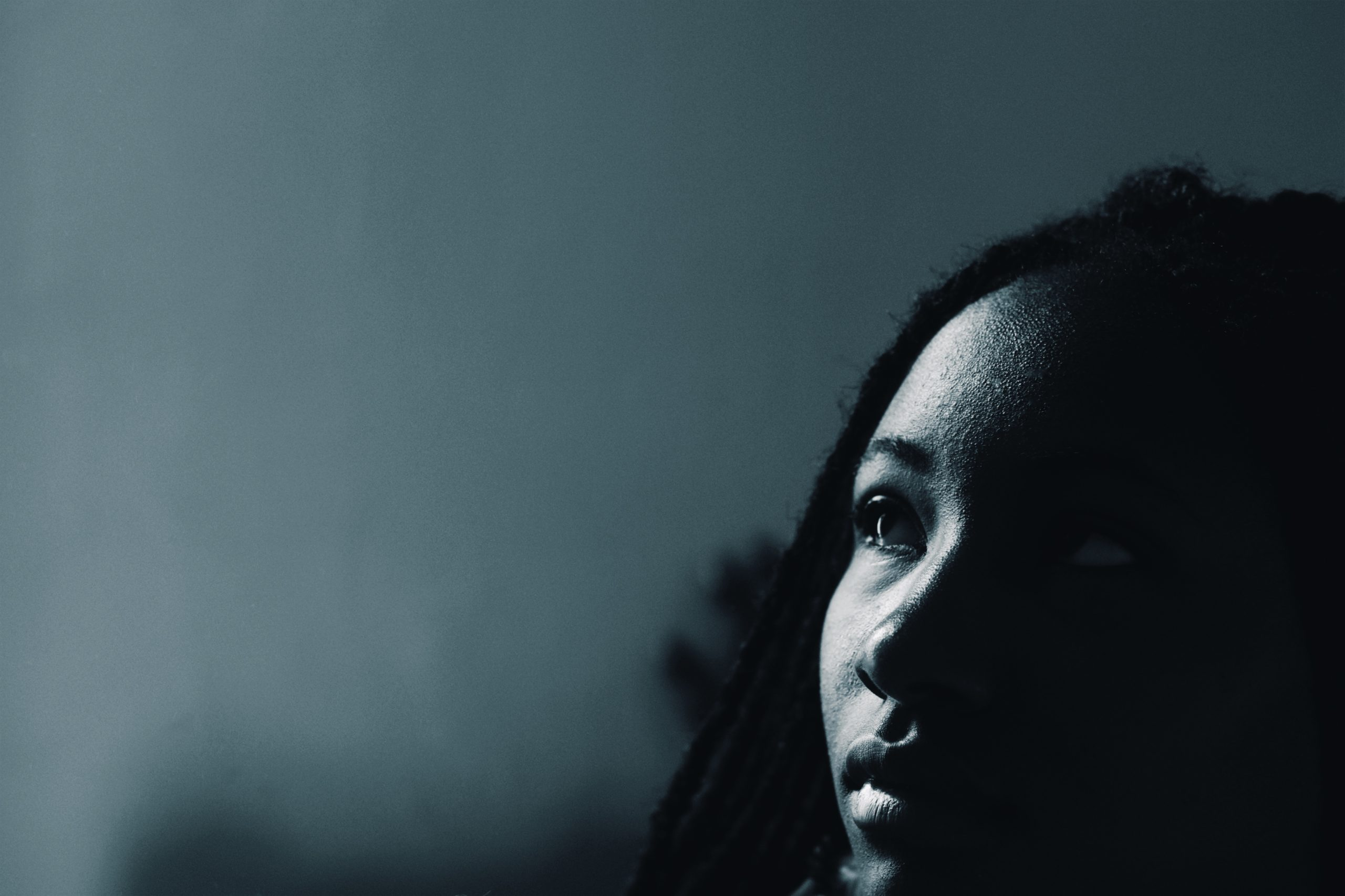 A blueish light shines on the face of a dark-skinned black woman with black locks, so that have of her face reflects the light, and half is cast in shadow. She looks out towards an empty space, looking serious and thoughtful.