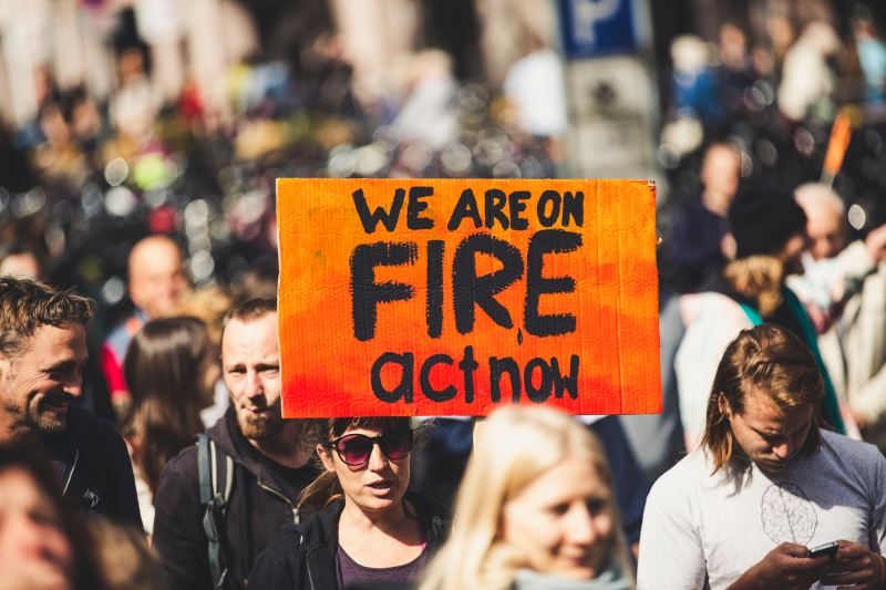 """A crowd of people at an outdoor protest marches forward. A woman wearing sunglasses holds an orange and red sign that says in big black letters, """"We are on FIRE, act now"""""""