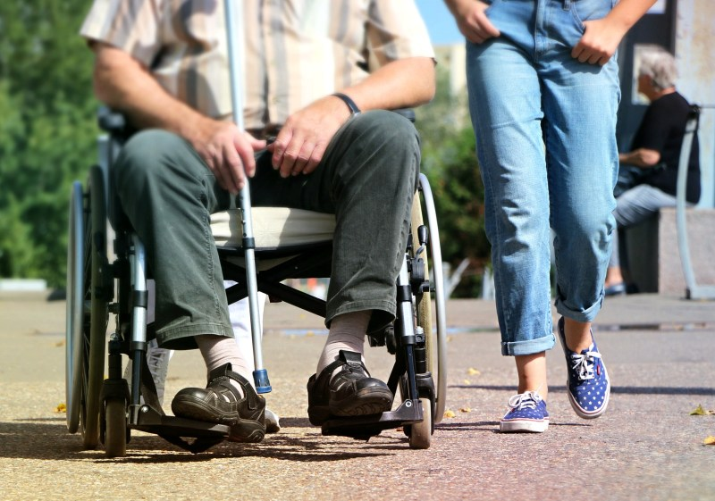 A young person wearing blue jeans and blue and white polkadot sneakers walks casually beside a person sitting in a wheel chair, holding a cane, as if they are enjoying an afternoon together outside in the sun.