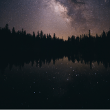 A large body of water at night framed by a dense row of fir trees, and a galaxy of stars above, which are also reflected in the water below.