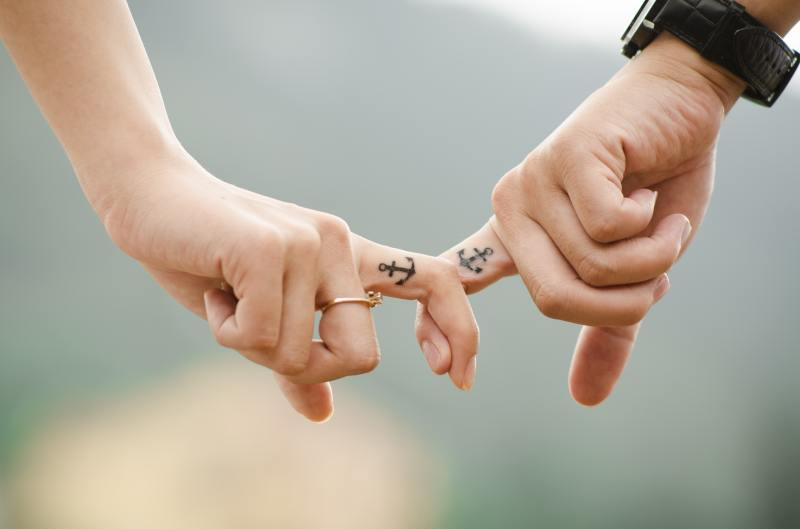 Two light skinned hands from different people clasp just their pointer fingers together, showing a tattoo of a black anchor on the side of their fingers.