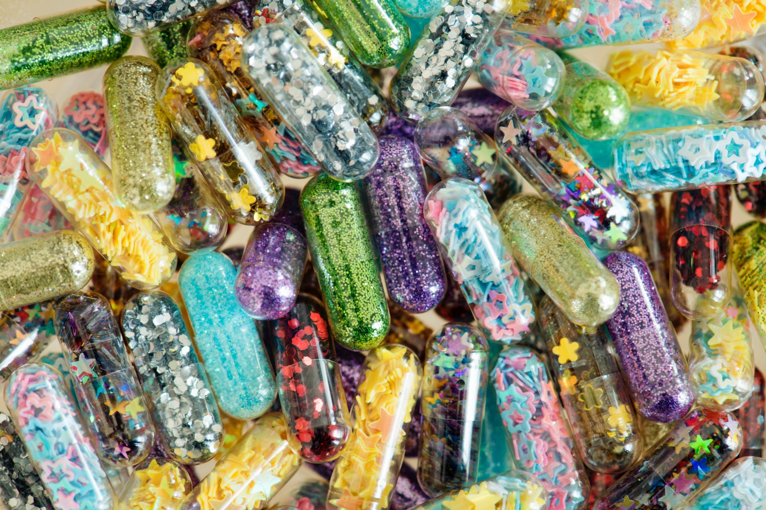 A pile of clear gelatin capsules filled with many different types of glitter: multicolored stars, tiny sparkles, little circles, flowers etc.