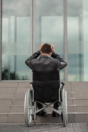 a man sits in a wheel chair at the bottom of a flight of stairs, looking exasperated at the lack of ramp.