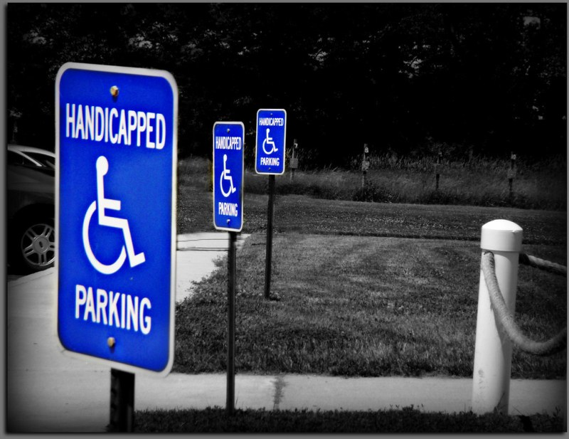 """Along the grassy front of a parking lot, there are three signs that say """"Handicapped parking"""" with a wheelchair symbol. The photo is in black and white except for the blue parking signs."""