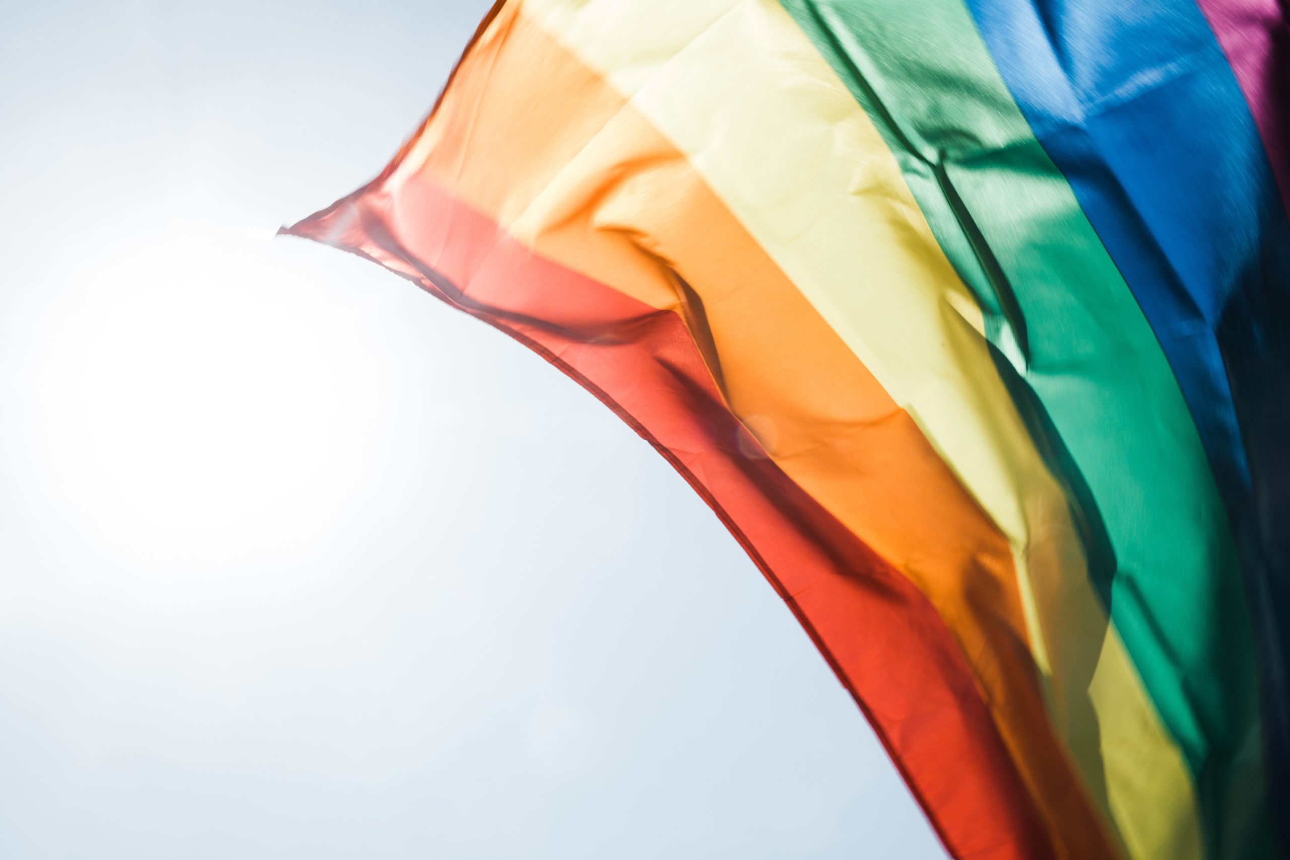 A rainbow flag looks slightly thin and faded with the sun shining through it, a very pale blue sky behind it.