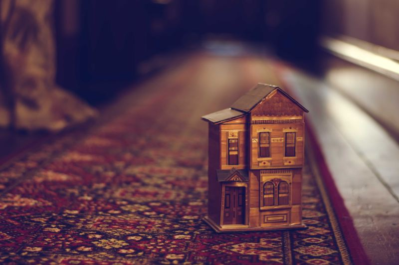 This tiny house trend is getting ridiculous. On top of a long intricately woven rug of black, white, and red, a tiny model house sits close to the viewer as the rug fades off into the distance. The house is made of a dark golden brown wood, it has two stories, a sloped roof, and many detailed decorations.