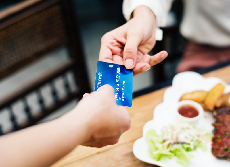 A person sitting at dinner hands a bright blue credit card to their server to pay for their meal.