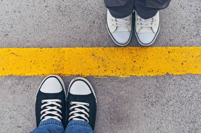 A yellow line on the cement forms a boundary between two pairs of feet, one with white shoes, one with black shoes.