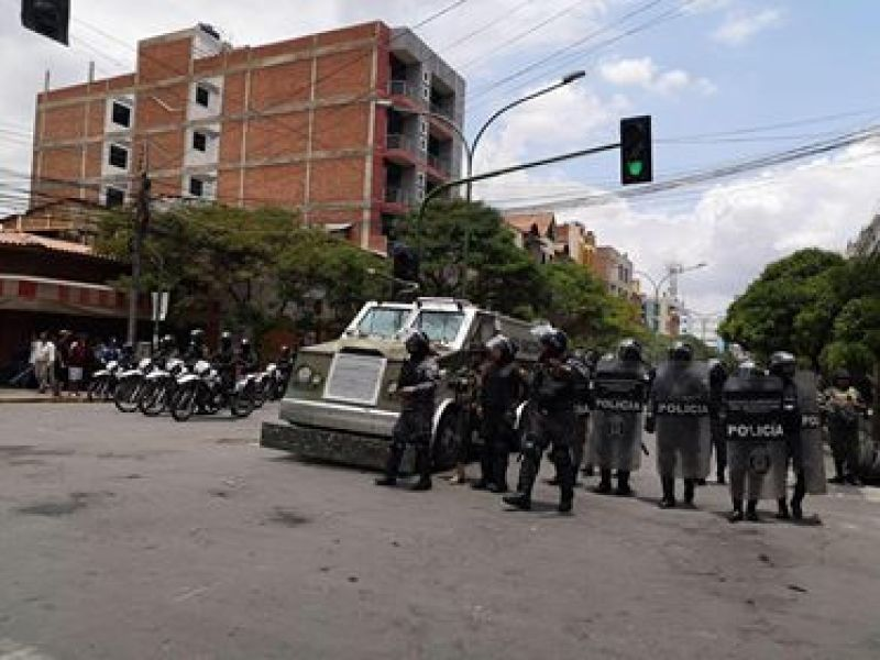 A line of Policía armed in black riot gear and a tank stand in the middle of the street at a protest inCochabamba, Bolivia.