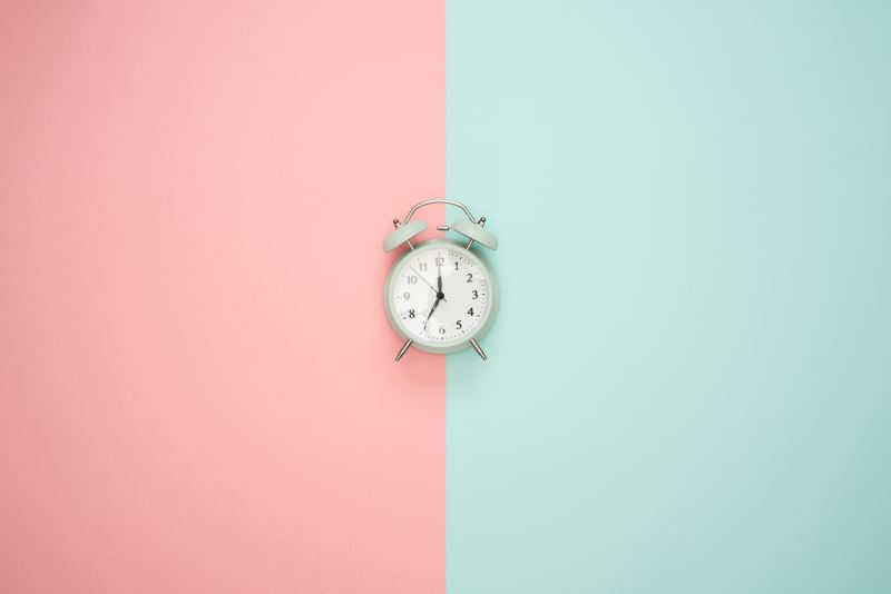 A background split down the center, one half is salmon pink, the other is muted teal. There is an off white alarm clock positioned directly in the center, the hands pointing to 7:00.