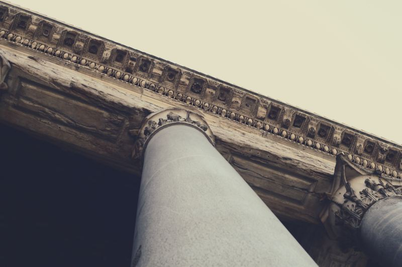 Looking up at several grey pillars at the corner of an ancient greek style building.