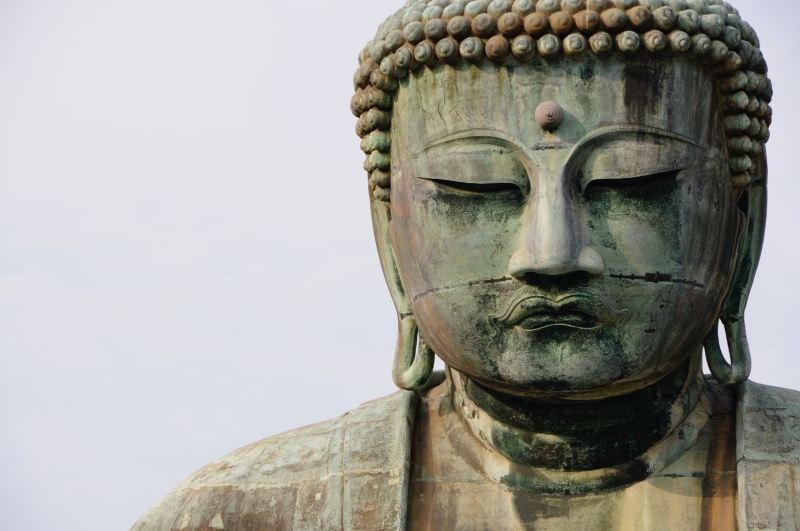 The face of a very large buddha statue, covered in rust and verdigris