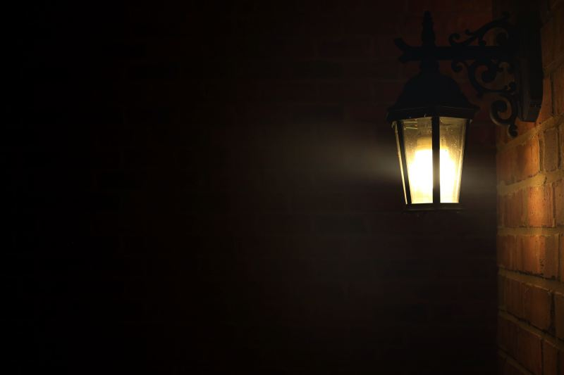A gas lamp is hanging from a black iron decorative hanger, mounted to a brick wall. The rest of the frame is pitch black, and the brick wall is only visible from the light of the lamp.