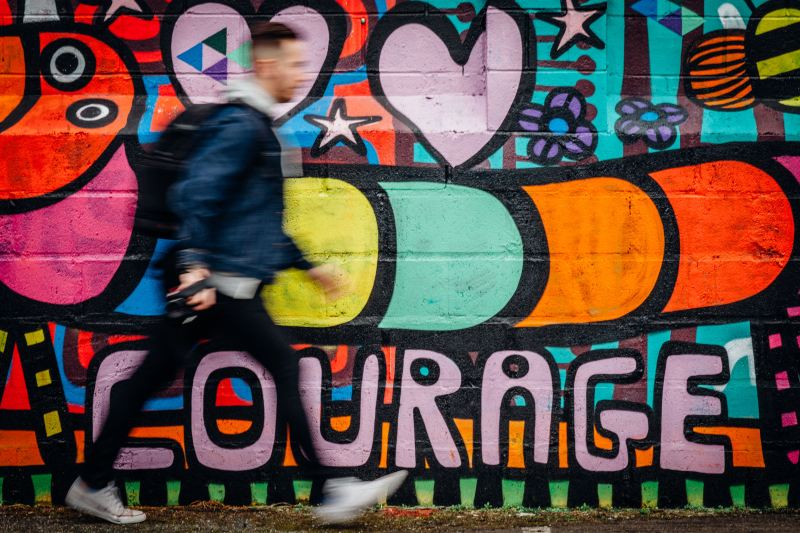 "A man walks rapidly in front of a brightly colored mural with a cartoon caterpillar, that says the word ""Courage."""