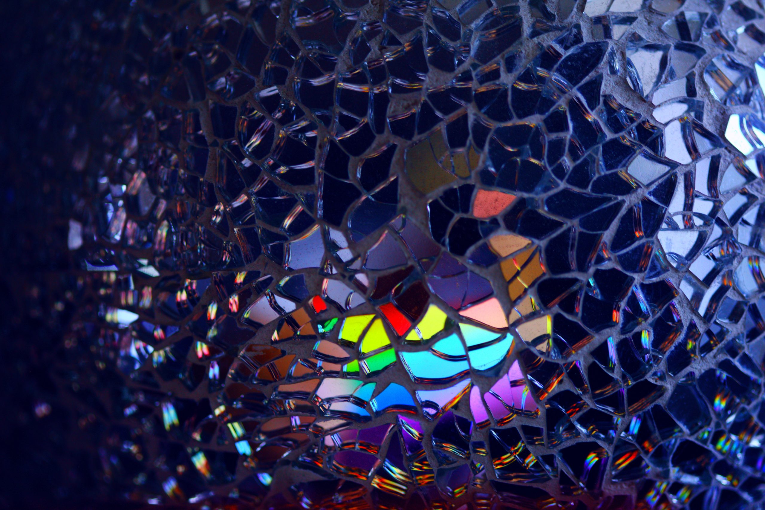 Closeup on a glass mosaic that looks all blue from one angle but reflects rainbow colors at another angle.