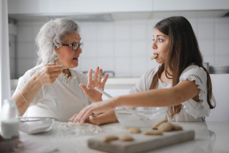 In a white kitchen, two light-skinned women wearing white, talk while making cookies. One is a woman in her 70's who seems to be giving advice to the other, who is in her teens, with a cookie in her mouth.