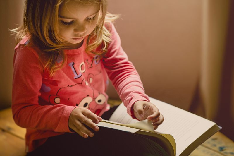 "A blonde 4-year old child wearing a pink long sleeve shirt that says ""love"" on it, sits with a book in her lap, carefully turning the page."