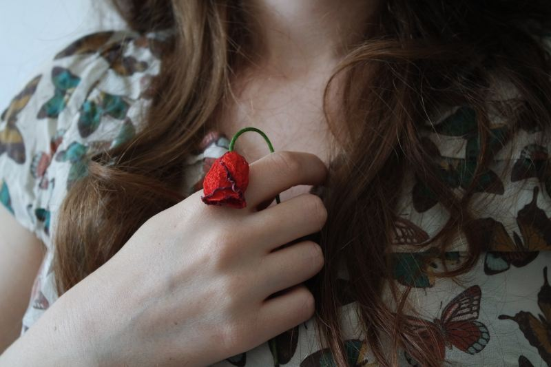 A woman with long brown hair clutches a sad wilted rose to her chest gently.