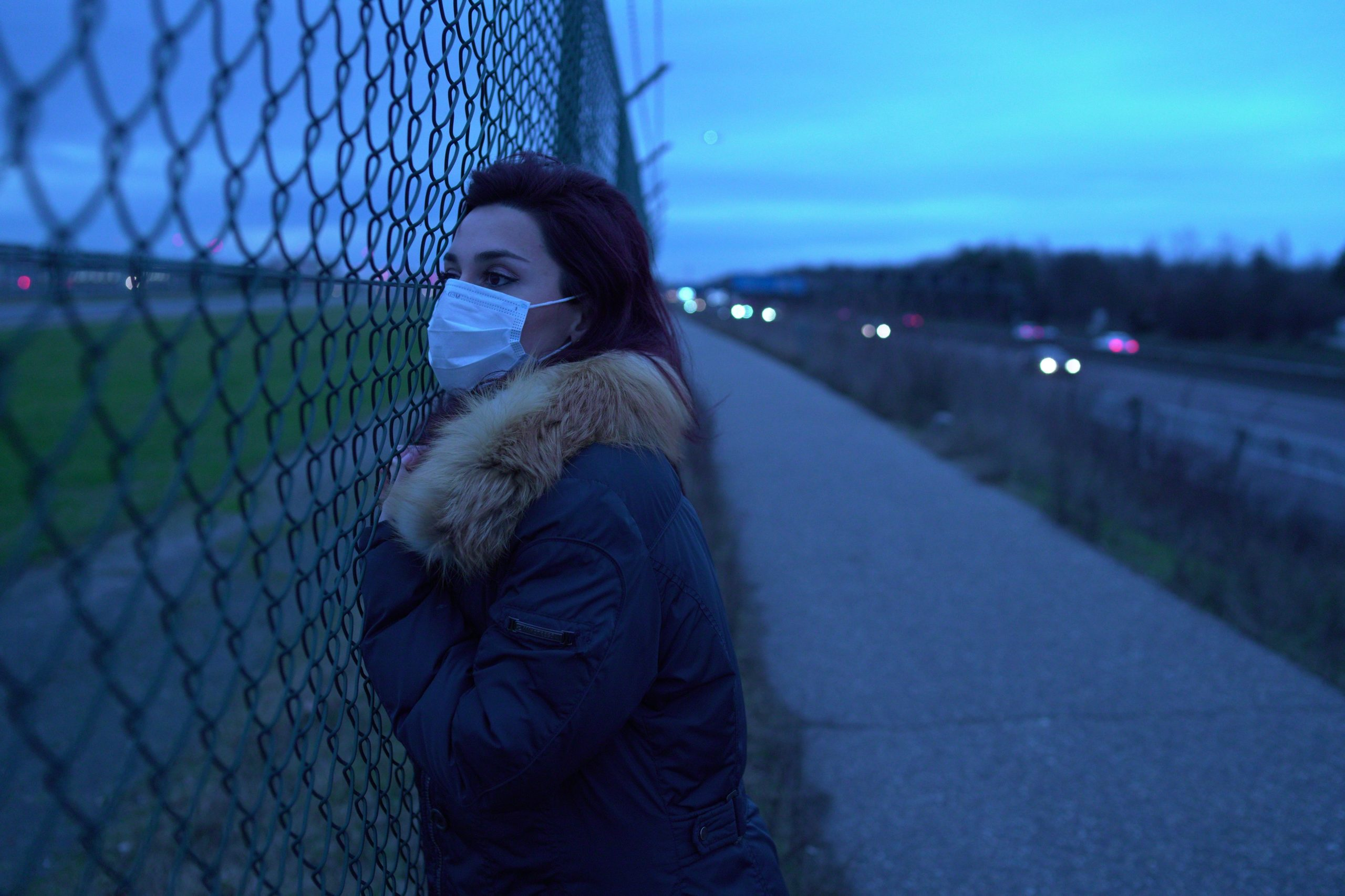 A light skinned woman wearing a medical mask leaning up against a wire fence, looking urgently into the distance, in the dim lighting of sun down.