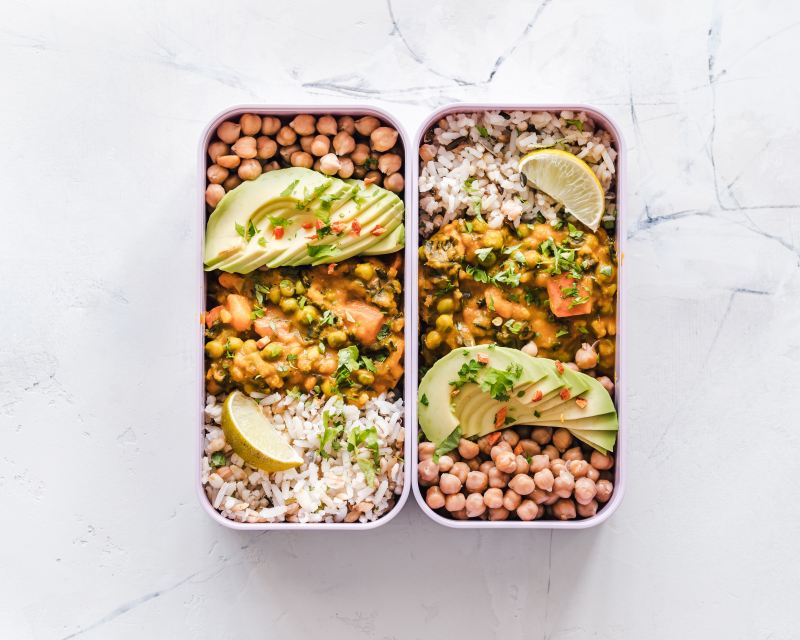 Two rounded rectangular plastic containers are filled with food bento-box style: There are garbanzo beans, rice, some kind of orange curry, avocado slices, and lemon and parsley as garnish.