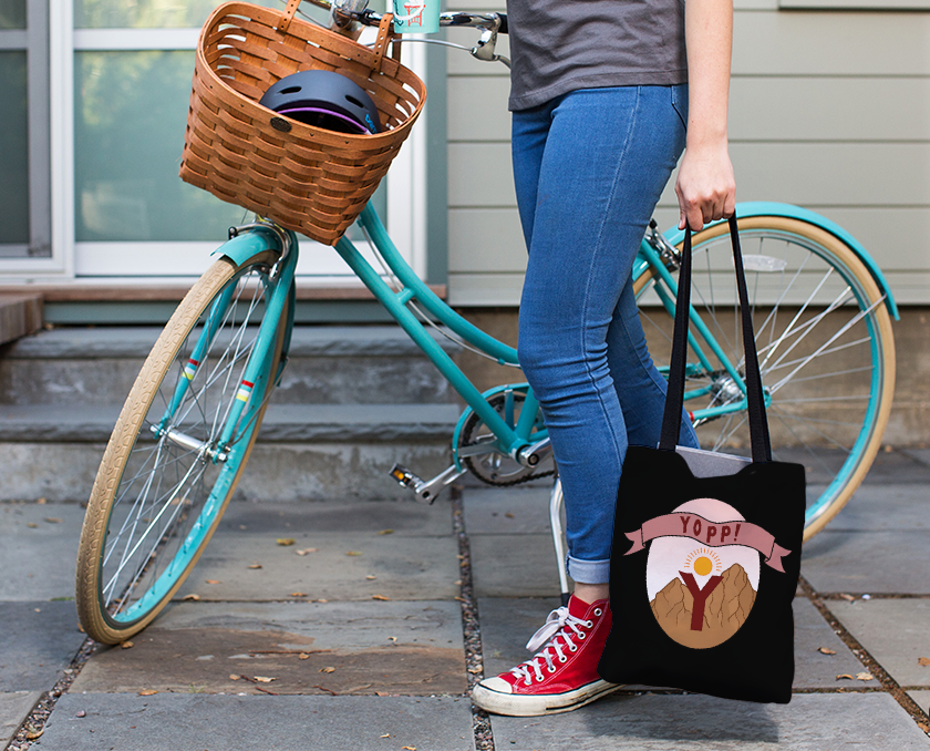 A person with a turquoise bicycle holding a black tote bag that has yopp