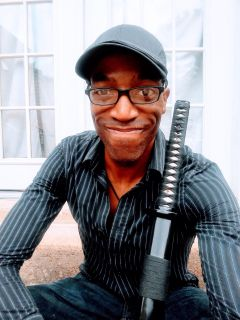A picture of Dennis R. Upkins, a lean black man with long limbs wearing a well fitted navy and white pinstripe button up shirt. He's wearing black framed glasses and a warm smile, and has a black katana leaning against his shoulder.