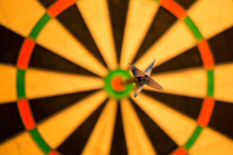 A black, orange, and green dart board in soft focus, a dart sticking exactly in the center of the bullseye, with only the head of the dart in focus.
