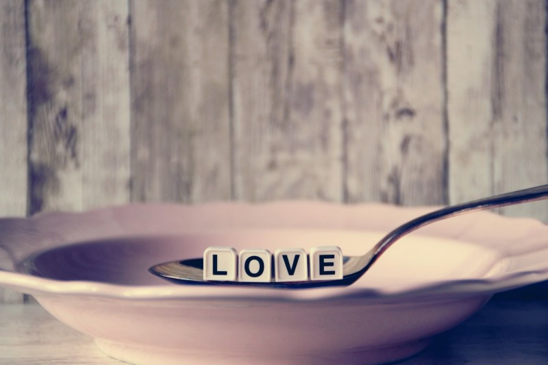 A silver spoon is lowered into a pink bowl, and in the spoon, five square white beads with black letters spell LOVE.