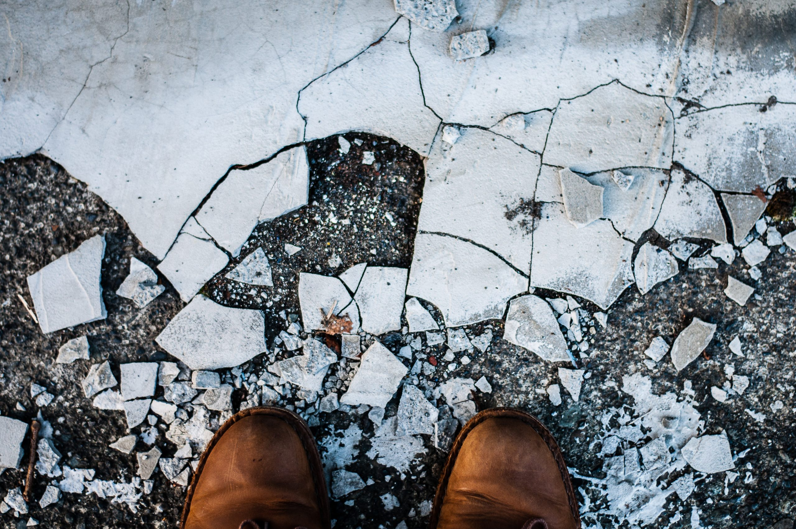 Two feet with brown shoes stand in front of a slap of concrete, which has shattered and becomes more broken and less identifiable as concrete the closer it gets to the shoes.