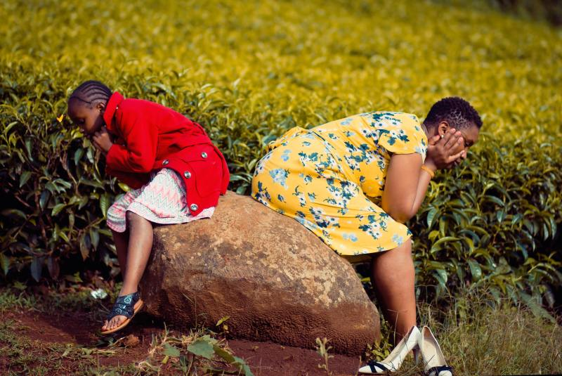 Two African women with short natural hair and brightly colored dresses sit back to back on a large boulder, holding their faces in their hands, looking at the ground in opposite directions.