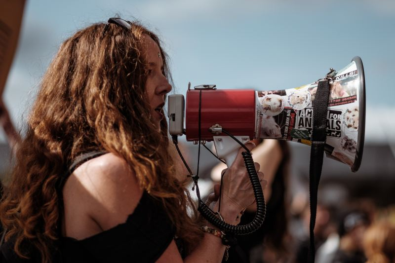 A woman with long curly reddish brown hair speaks into a megaphone to a large crowd of protesters.