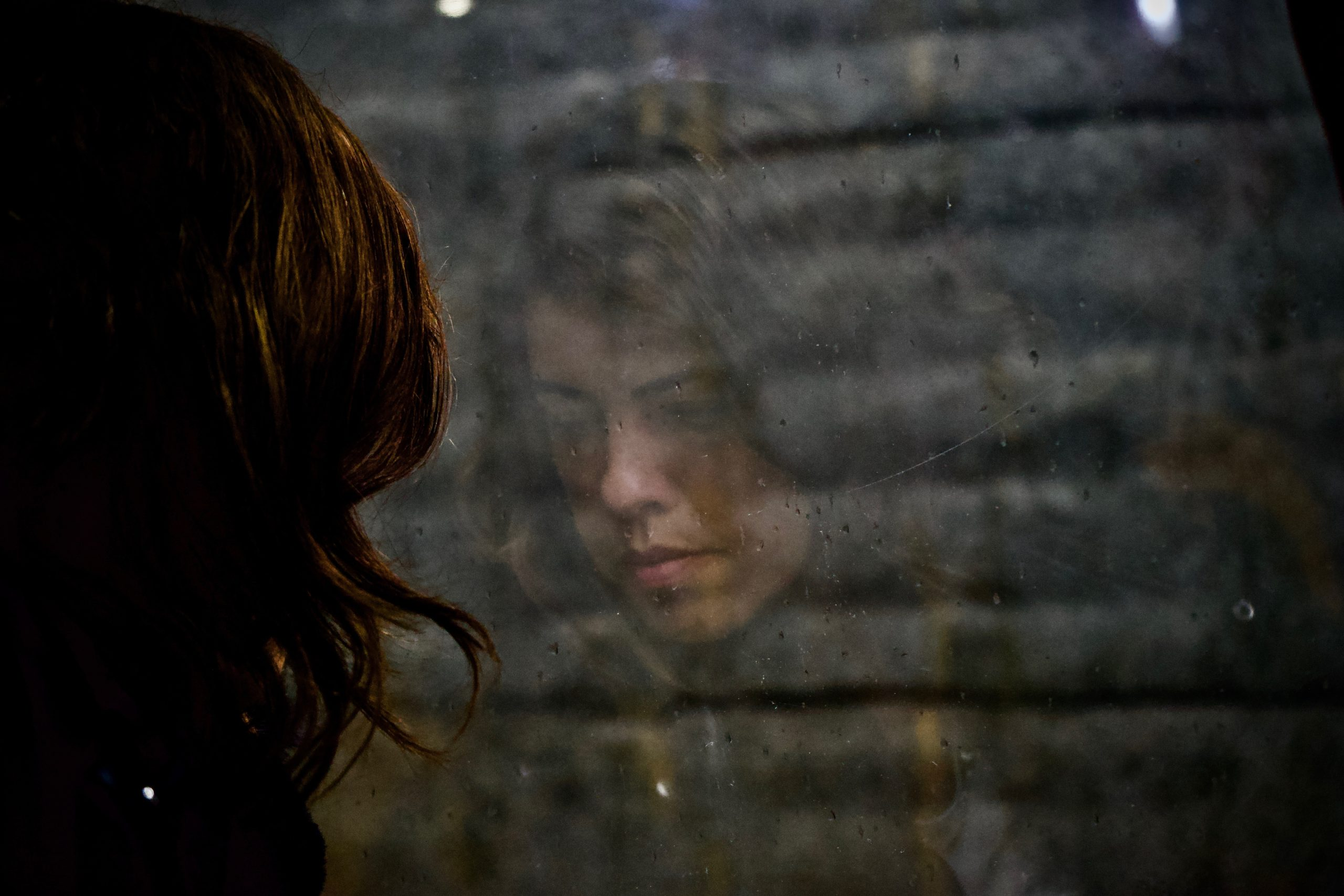 A light skinned woman with dark brown hair is pictured from the back. We can only see her face faintly in the reflection of the window in front of her.