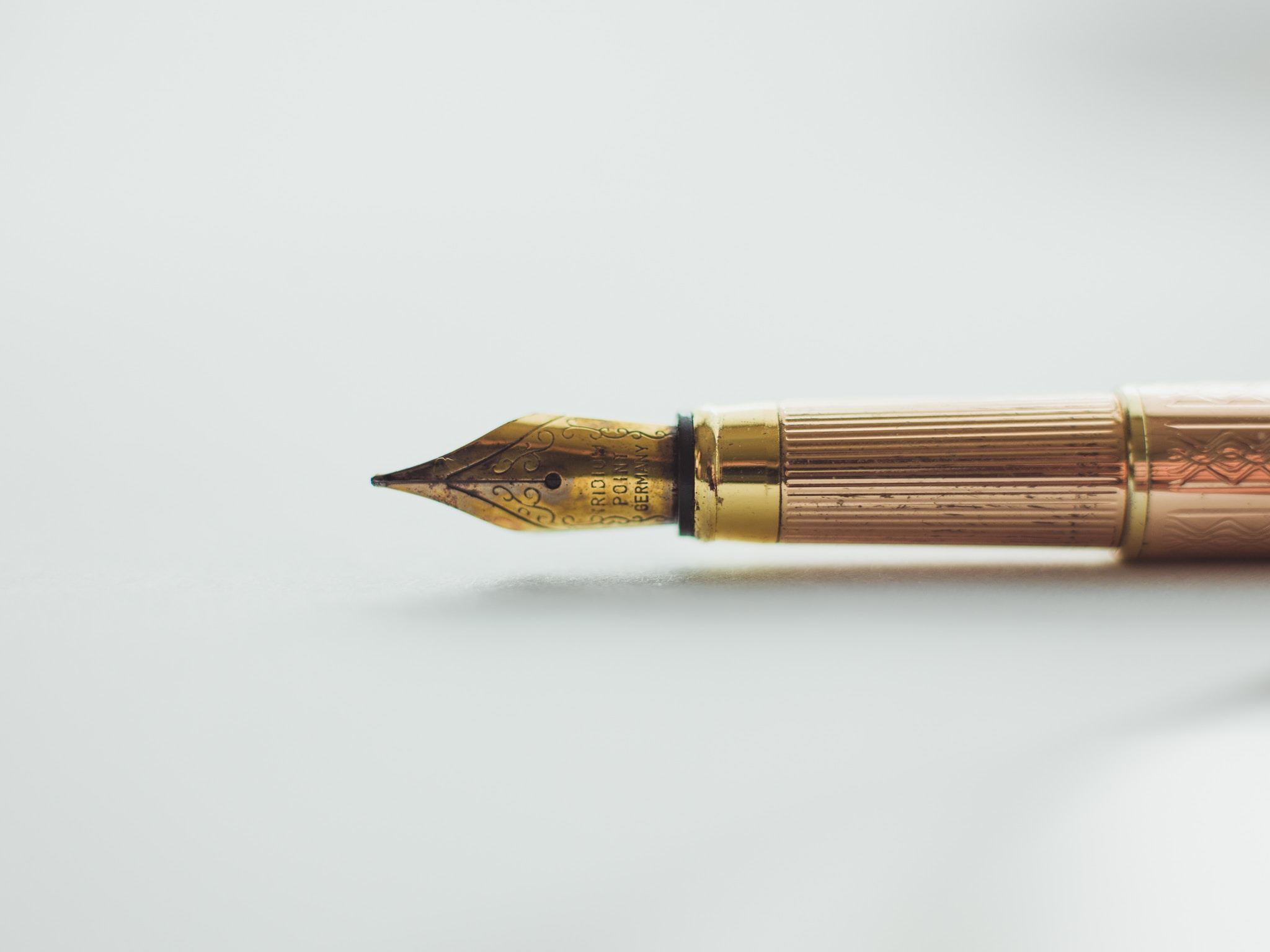 An old fashioned decorative ink pen plated in gold and copper colored metals.