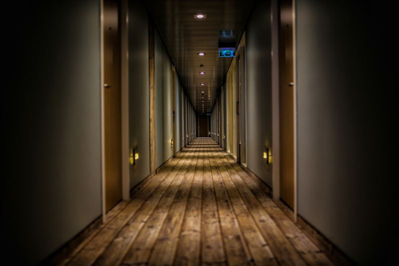 A head on shot of a long dimly lit hallway with rows of doors on either side and a wooden floor. It looks like the rows of doors go on forever into the distance.