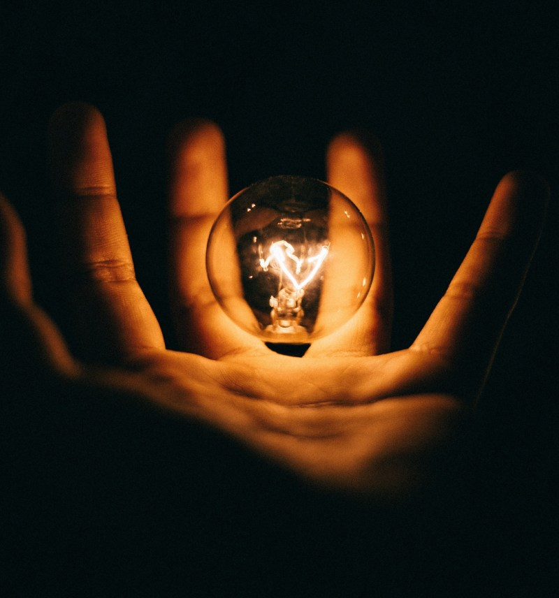 The shape of a hand is illuminated by the small light bulb floating inside it.