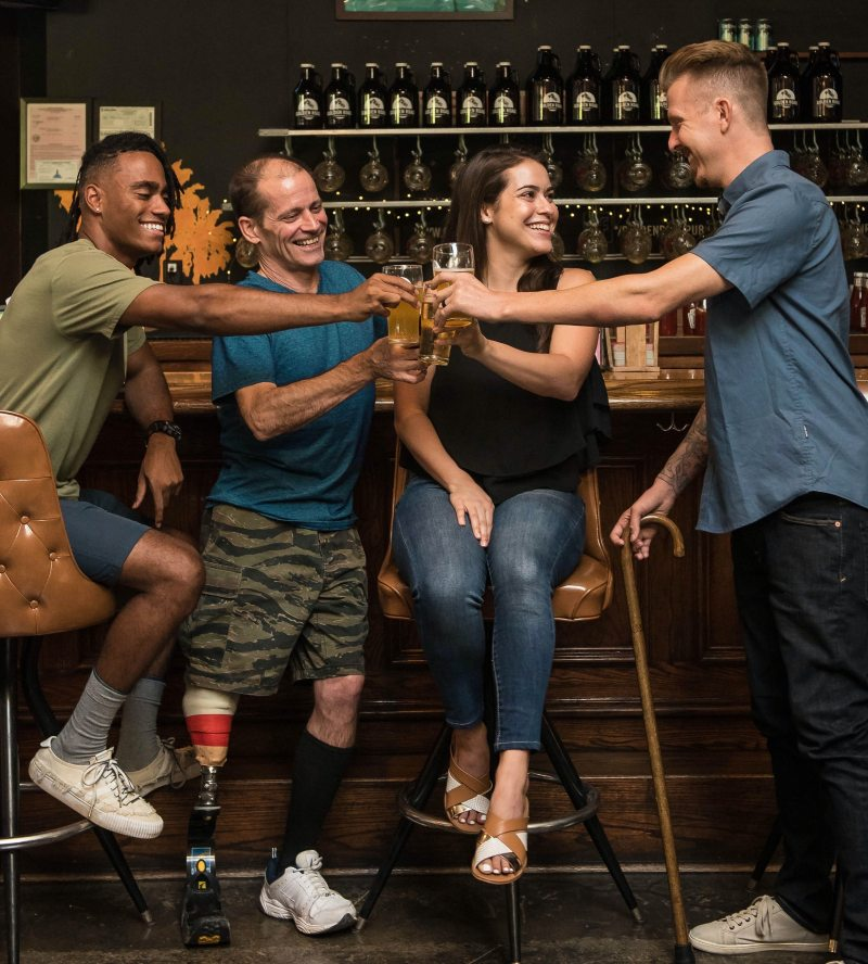 Four people of different skin tones dressed casually sit next to a bar, cheersing their glasses of beer. One man has a prosthetic mechanical leg, another is holding a wooden cane, the other two are sitting on bar stools.