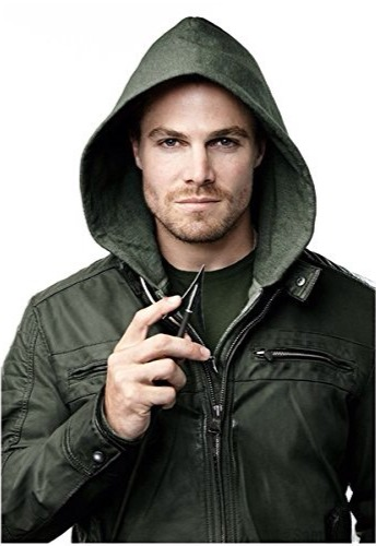 Character Oliver Queen: A white man in his mid-30's with reddish stubble and a sparse mustache, staring intensely at the camera with his brown eyes. His hair is concealed by a camo green hooded, zip up jacket, and he is holding an arrow in front of him.